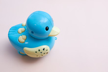 Blue Plastic Duck A Over Pink Background. Children's Toy Duck Made Of Plastic With Light Music Moving On The Surface. Flat Lay. Copy Space.