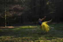 Girl Wearing Princess Costume Levitating Over Field At Forest