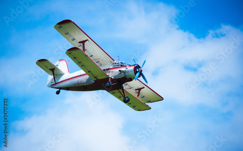 Photo Biplane airplane flies in a picturesque cloudy sky