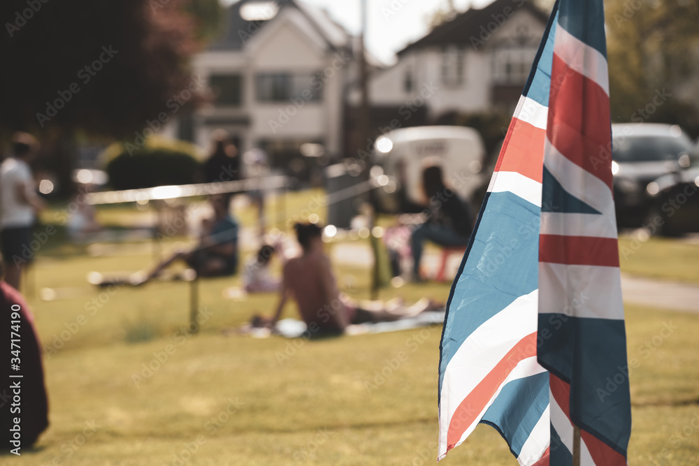 Fototapeta Vitage style Union Jack flag flying in front of VE Day celebrations at a social distance street party in May 2020