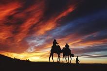 Scenic View Of Men On Camels In Desert