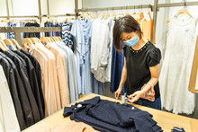 Asian Woman Shopping Apparels In Clothing Boutique With Protective Face Mask As New Normal Requirement