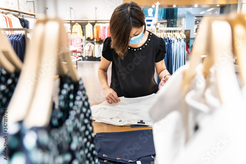 Fotografia Asian woman shopping apparels in clothing boutique with protective face mask as