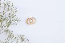 Flowers And Two Golden Wedding Rings On White Background. Top View.