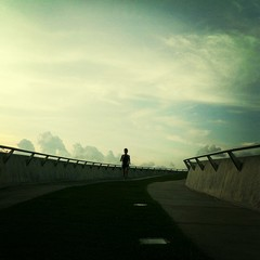 Man Running On Footbridge Against Sky