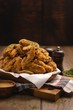 canvas print picture - Vertical shot of a pile of fried chicken wings and some spices on a wooden table