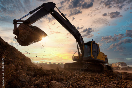Photo excavator at sandpit during earthmoving works in the construction site