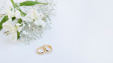 Flowers And Two Golden Wedding Rings On White Background.