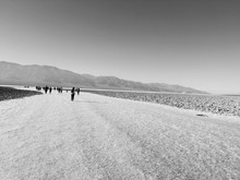 People Walking On Salt Flats At Death Valley National Park Against Clear Sky