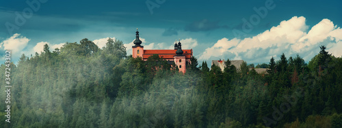 Fotografie, Obraz beautiful little church over misty forest, in the background blue sky with white