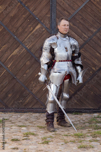 Valokuvatapetti Knight infantryman in armor and with a sword shows combat strikes