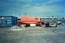 Orange Lifeboat Moored In Harbor Against Sky