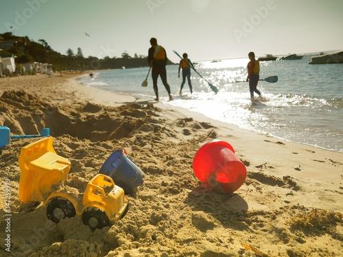 People With Oars Walking On Beach Fototapeta
