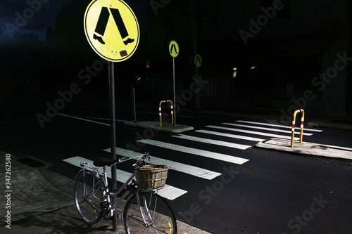 Fotografiet Bicycle Parked To Pole Against Crosswalk