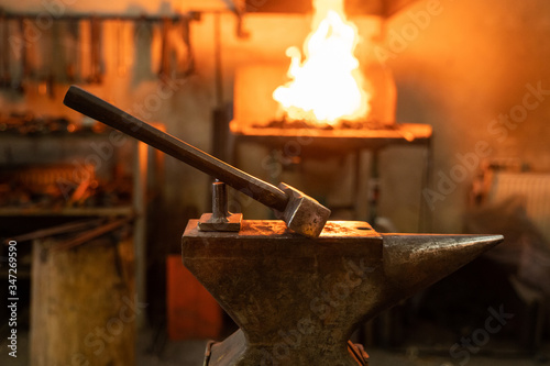 Hammer and anvil in forge on blurred background Wallpaper Mural