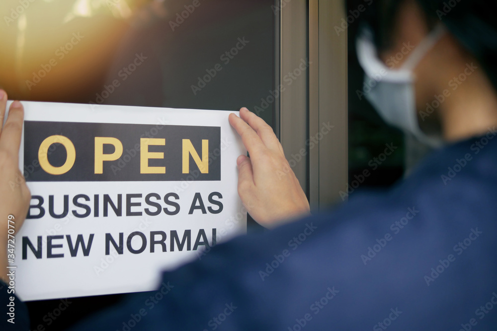 """Fototapeta Reopening for business adapt to new normal in the novel Coronavirus COVID-19 pandemic. Rear view of business owner wearing medical mask placing open sign """"OPEN BUSINESS AS NEW NORMAL"""" on front door."""