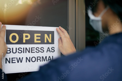"""Fototapeta Reopening for business adapt to new normal in the novel Coronavirus COVID-19 pandemic. Rear view of business owner wearing medical mask placing open sign """"OPEN BUSINESS AS NEW NORMAL"""" on front door. obraz"""