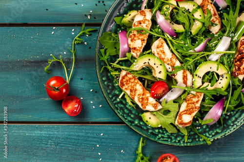 Fototapeta The concept of oriental cuisine. National Cyprus Salad with grilled Halloumi cheese, tomatoes, avocado, arugula. banner menu recipe place for text. Flat lay obraz