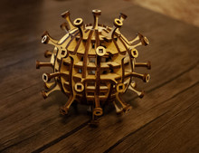 The Image Of A Coronavirus Particle Made Of Wood. Woodcraft Coronavirus. Wooden Virus. Woodcraft Art. Covid-19