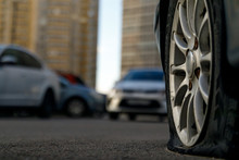 Car Tire With A Flat Tire In The Yard Near A Multi-storey Building. Image Of An Accident, Damage, Breakdown For Illustration On The Topic Of Repair, Insurance. Selective Focus.