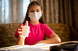 Girl in pink t-shirt and medical mask showing hand santizer to the camera
