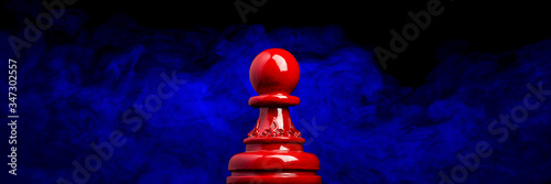 Obraz na plátně Macro image of a wooden chess pawn in red with blue and black smoky background