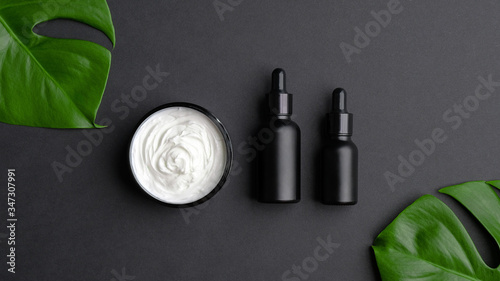 Fototapeta Set of luxury cosmetic products on black background top view. Flat lay natural body cream, black clean dropper bottles mockup and tropical monstera leaves. SPA natural organic beauty products. obraz