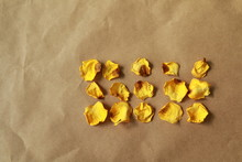 High Angle View Of Dry Yellow Rose Petals On Brown Paper