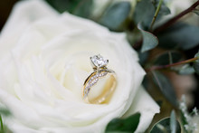 An Engagement Ring And Wedding Band Sitting Upright On A White Rose, Close-up Macro Shot.