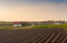 View Of A Freshly Plowed Field With The Malopolska Regional Train In The Background.