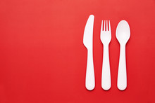 Plasic White Cutlery Set With Red Background. Top View