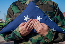 Folded American Flag With Stars Showing Being Held By Soldier In Camouflage Fatigues,. Military Funeral Or MIA/POW Ceremony