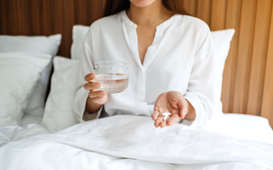 Closeup image of a sick woman holding white pills and a glass of water while lying down on a bed