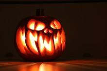 Close-up Of Illuminated Jack O Lantern Against Black Background