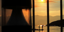 Silhouette People On Diving Platform In Sea Seen Through Widow During Sunset
