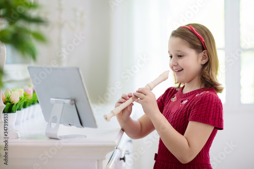 Cuadros en Lienzo Child playing flute. Remote learning.
