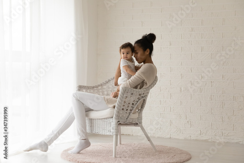 Loving young biracial mother sit in chair in living room hold hug small newborn Canvas Print