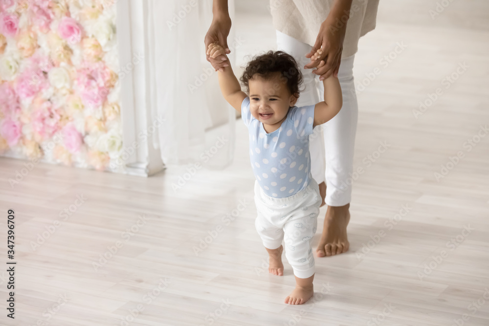 Fototapeta Smiling little biracial toddler infant child make first steps at home holding mom hands, happy small african American baby learn walking with mother support and care, upbringing, childcare concept