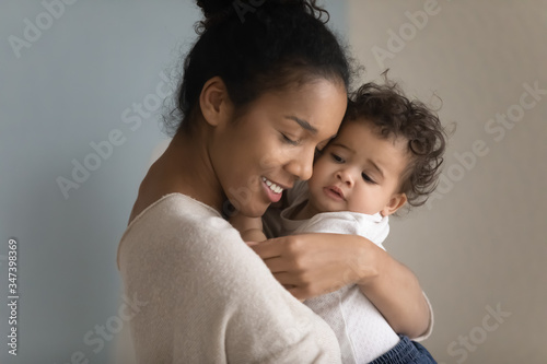Close up of loving biracial young mom hug cuddle little ethnic infant toddler, h Canvas Print