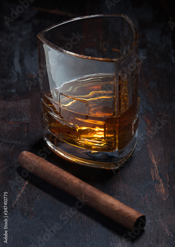 Single malt scotch whiskey in luxury crystal glasses with cuban cigar on wooden background