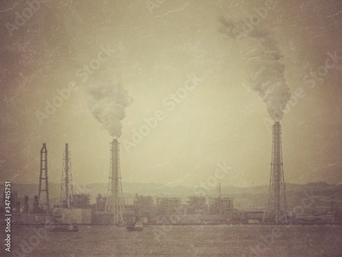 Smoke Emitting From Chimneys By Sea Against Clear Sky Fototapete