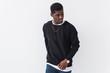 Leinwandbild Motiv Street fashion concept - Studio shot of young handsome African man wearing sweatshirt against white background with copy space.
