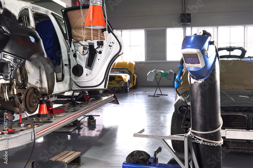 Welding equipment in a car repair station, helmet hanging on a gas tank, no peop Canvas Print