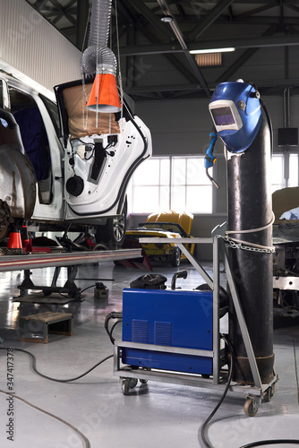 Photo Welding equipment in a car repair station, helmet hanging on a gas tank, no peop