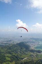 People Paragliding Over Landscape Against Sky