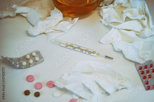 Fototapeta Cup of tea and a thermometer on the white table with pills and napkins from runn