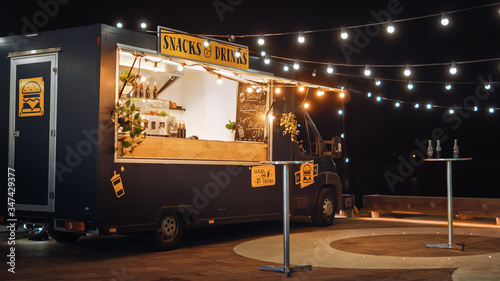 Tablou Canvas Empty Scene with a Dark Street Food Van Standing in the Evening in a Nice Warmly Lit Neighbourhood Next to the Sea
