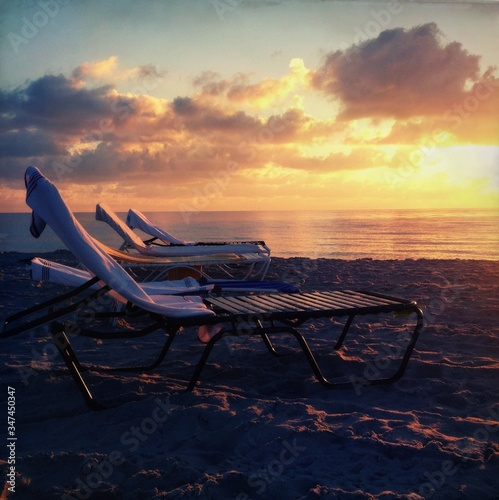 Photographie Empty Deck Chairs At Beach Against Sky During Sunset