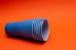 Leinwanddruck Bild - blue plastic cups on an orange paper background