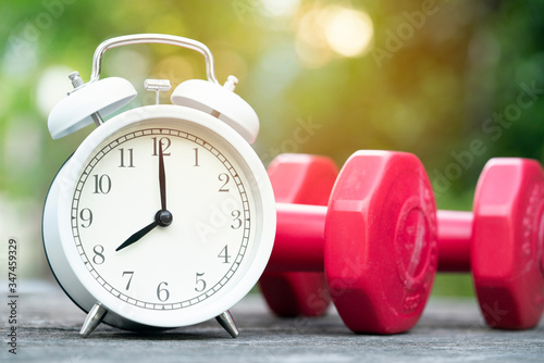 Time for exercising alarm clock and dumbbell on the table background Canvas Print